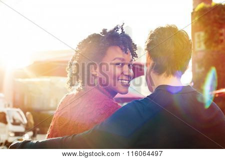 Happy african woman and young man sit on bench while looks at camera in a cafe. Close up of loving couple sitting in a cafeteria. Young smiling woman with friend looking at camera.