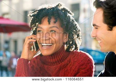 Close up shot of a young african woman sitting with friend talking on phone. Young couple enjoying a good news received over phone. Laughing girl having a nice conversation on mobile phone.