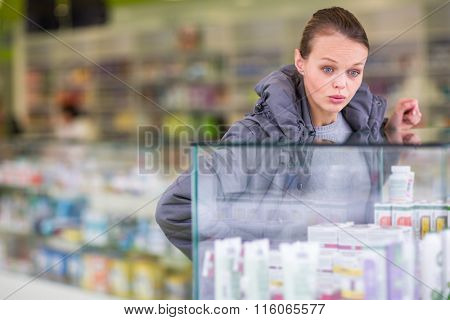 Young woman looking for the right pills in a modern pharmacy (shallow DOF; color toned image)