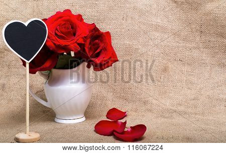 Red Roses And Mini-board In The Form Of Heart In A White Jug Against A Sacking