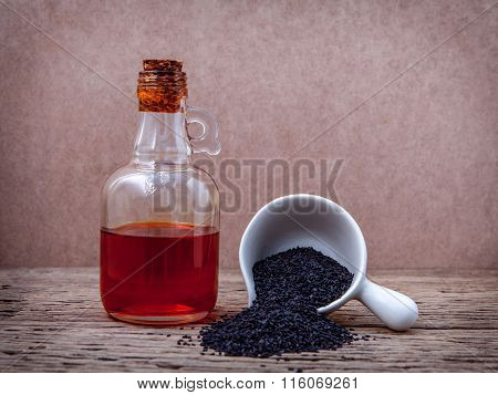 Black Sesame Oil And Sesame Seeds In White Bowl Set Up On Grunge Wooden Background.