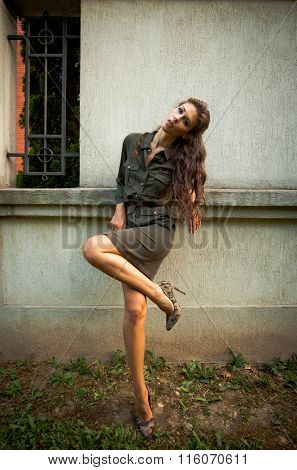 young woman in military style short fashion dress and high heel shoes lean on wall, day shot, natural light full body shot