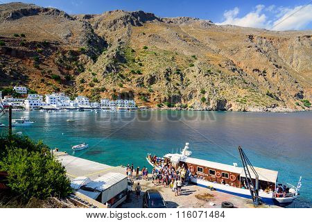 Small cruise ship unloading tourists at port of Loutro town on Crete island