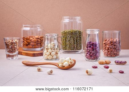 Various Beans And Nuts In The Glass On Brown Background. Mung Bean, Groundnut, Red Kidney Bean , Lot