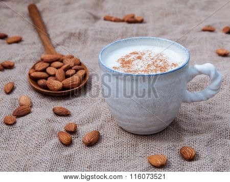 Homemade Almond Milk In The Coffee Cup With Almond In The Wooden Spoon Setup On Cloth Sack Backgroun
