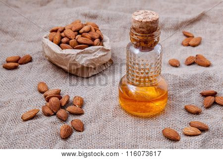 Bottle Of Essential Almonds Oil With Almonds  On Cloth Sack Background.