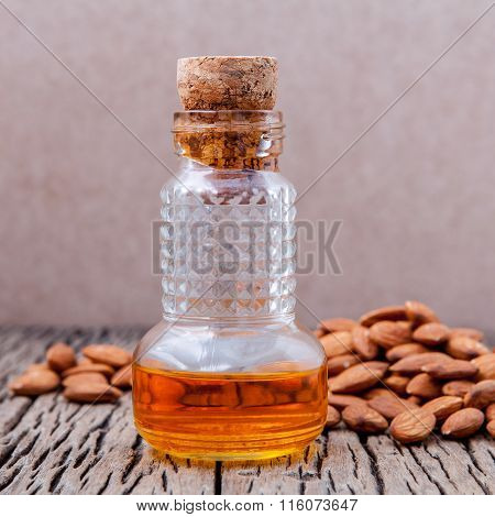 Bottle Of Essential Almonds Oil With Almonds On Wooden Background.