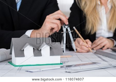 Architects Working On Blueprint With House Model On Desk