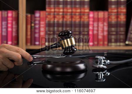 Judge Striking The Gavel At Table Against Bookshelf
