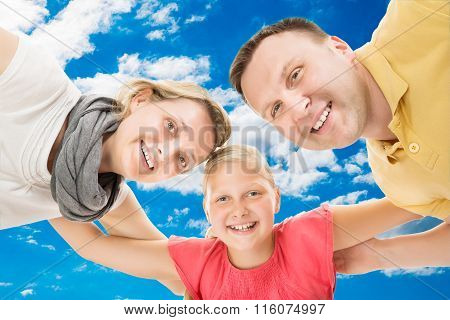 Happy Parents With Daughter Forming Huddle Against Sky