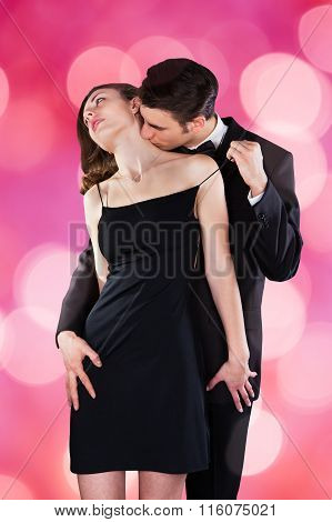 Man Kissing Woman's Neck While Removing Shoulder Strap