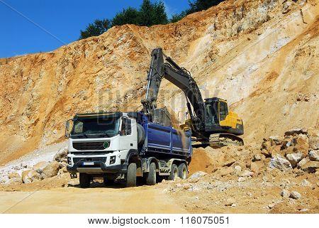 Yellow excavator and big truck