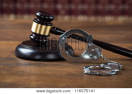 Mallet And Handcuffs On Table In Courtroom