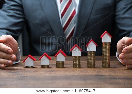 Businessman Protecting House Models On Stacked Coins