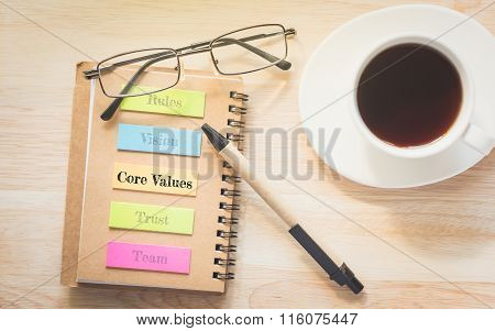 Core Value text on a sticky notes with glasses and pen.