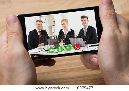 Businessman Video Conferencing With Colleagues On Smartphone