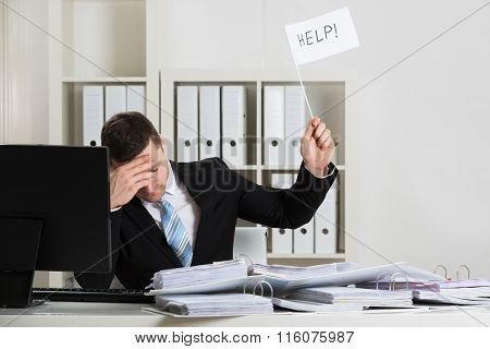 Overworked Accountant Holding Help Sign At Desk