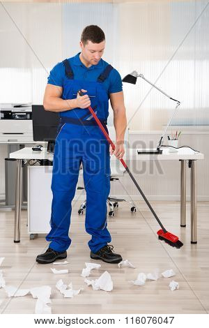Smiling Janitor Holding Broom In Office