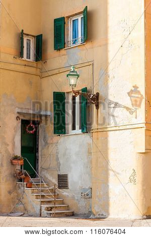 Shutters And Door On Ancient Mediterranean Facade With A Lamp Post