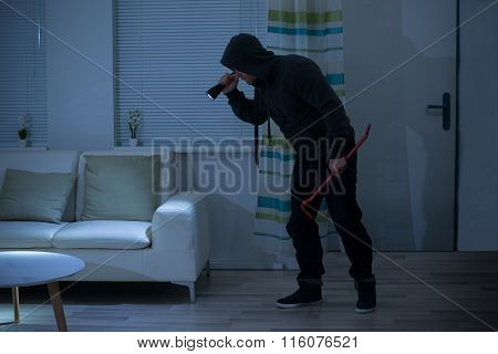 Robber With Crowbar And Flashlight In Living Room