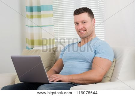 Portrait Of Man Using Laptop On Sofa At Home