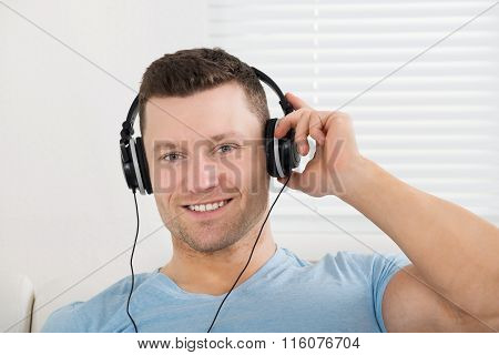 Smiling Man Listening To Music Through Headphones