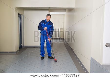 Worker With Broom Cleaning Office Corridor