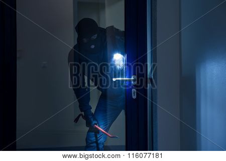 Thief With Flashlight Trying To Break Door