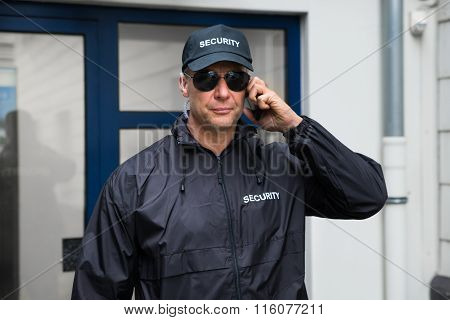 Confident Security Guard Using Mobile Phone Outside Building