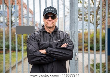Security Guard Standing Arms Crossed In Front Of Gate