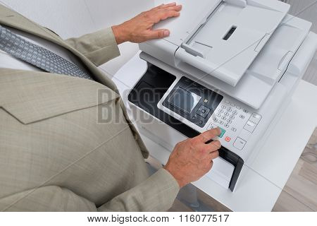 Businessman Pressing Printer's Button In Office