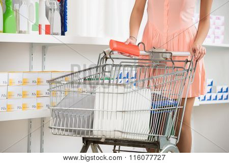 Woman With Shopping Cart Buying Beauty Product In Store