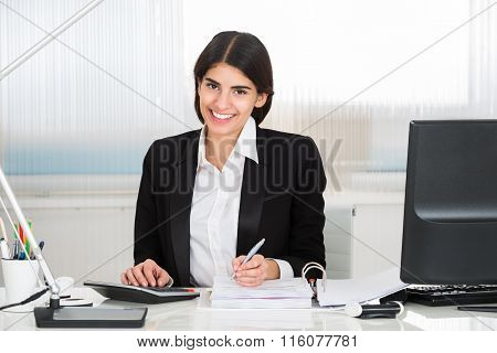 Accountant Calculating Finance With Calculator At Desk