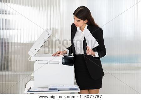 Businesswoman Using Photocopy Machine In Office