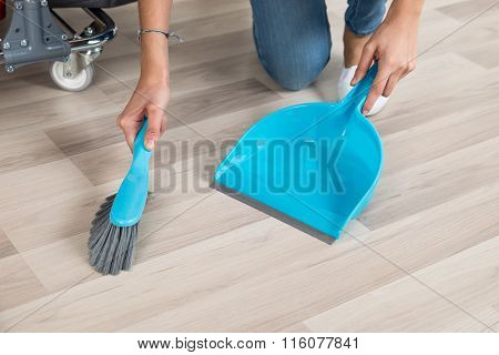 Cleaner Sweeping Floor With Broom And Dustpan In Office