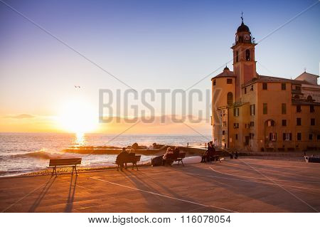 People Staring At The Sunset Near A Church In Front Of The Sea In Camogli, Near Genoa