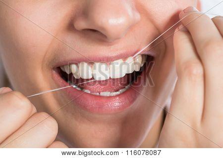 Woman Flossing Teeth At Home