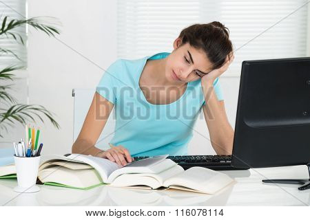 Tired Student With Hand On Head Studying At Home