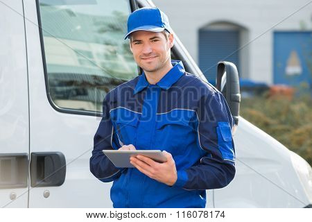 Delivery Man Smiling Using Digital Tablet By Truck
