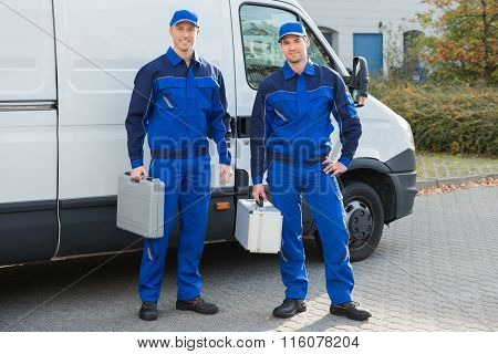 Confident Technicians Standing Against Truck