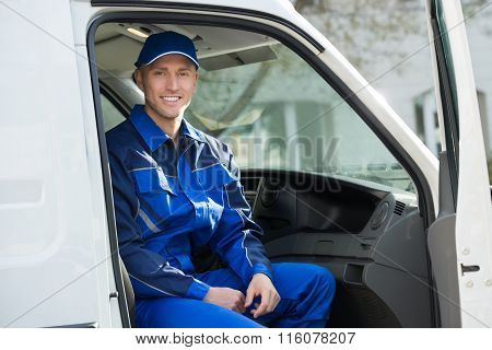 Portrait Of Happy Technician Sitting In Van