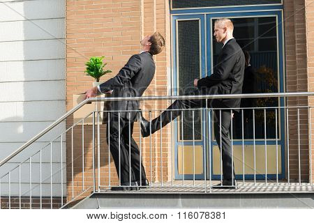 Businessman Kicking Employee With Belongings Outside Office