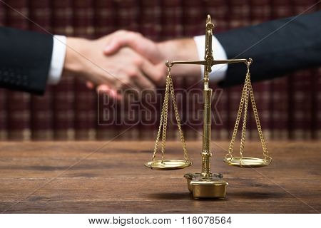 Justice Scale On Table With Judge And Client Shaking Hands