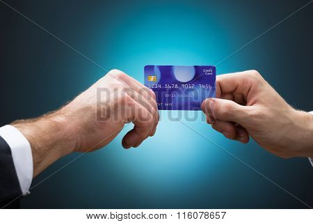 Businessmen Holding Credit Card Against Blue Background