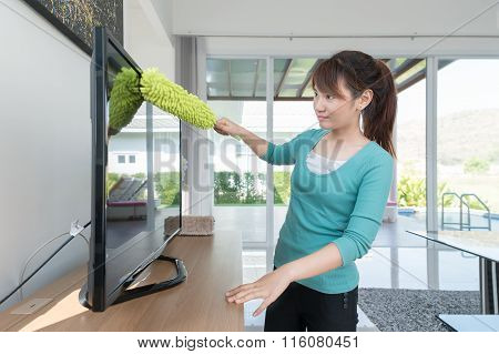 Asian Young Woman Cleaning Dust On Tv At Home