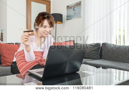 Young Asian Woman Sitting On Couch Shopping Online