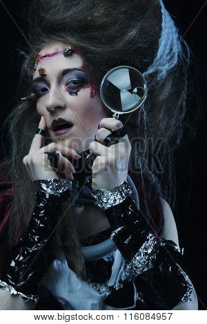 woman with creative make up holding a magnifying glass