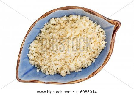 macadamia nut flour in an isolated leaf shaped ceramic bowl, top view