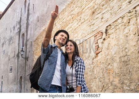 Young couple exploring an old town. Man pointing at some landmark.