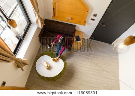 Top view of woman putting down the watr cup and holding a cellphone